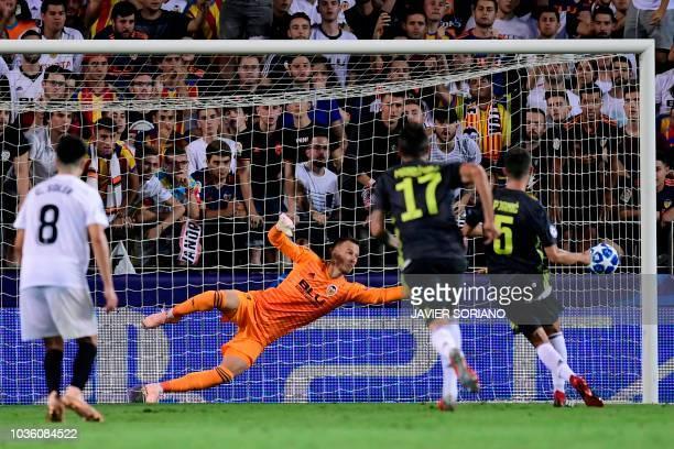Juventus' Bosnian defender Miralem Pjanic scores against Valencia's Brazilian goalkeeper Neto during the UEFA Champions League group H football match...