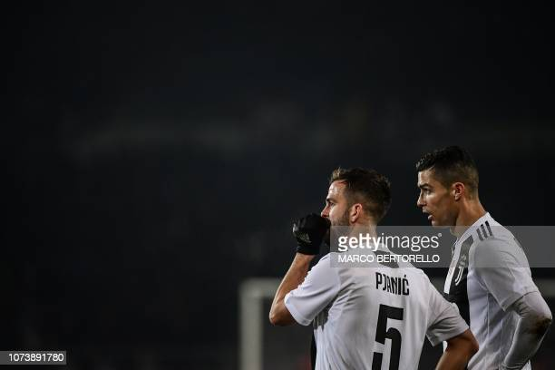 Juventus' Bosnian midfielder Miralem Pjanic and Juventus' Portuguese forward Cristiano Ronaldo talk during the Italian Serie A football match Torino...