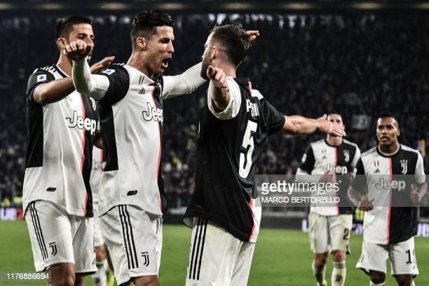 Juventus' Bosnian midfielder Miralem Pjanic celebrates with Juventus' Portuguese forward Cristiano Ronaldo and Juventus' German midfielder Sami...