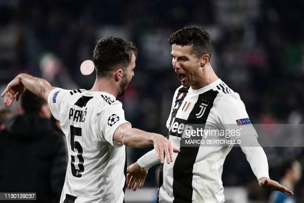 TOPSHOT Juventus' Bosnian midfielder Miralem Pjanic embraces Juventus' Portuguese forward Cristiano Ronaldo at the end of the UEFA Champions League...