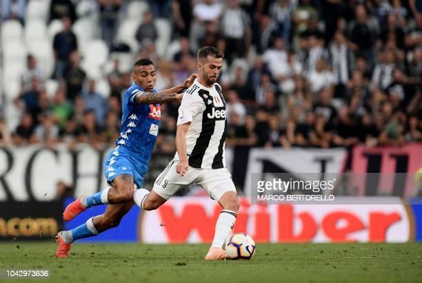 Juventus' Bosnian midfielder Miralem Pjanic outruns Napoli's Brazilian midfielder Allan during the Italian Serie A football match Juventus vs Napoli...