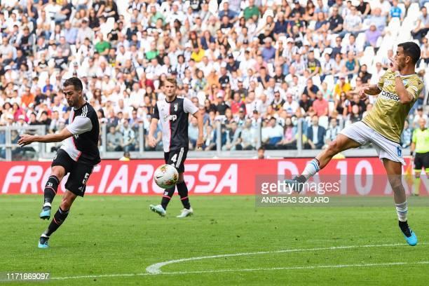 Juventus' Bosnian midfielder Miralem Pjanic shoots to open the scoring despite Spal's Italian midfielder Mirko Valdifiori during the Italian Serie A...