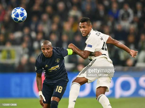 Juventus' Brazilian defender Alex Sandro heads the ball under pressure from Manchester United's English midfielder Ashley Young during the UEFA...