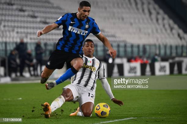 Juventus' Brazilian defender Alex Sandro tackles Inter Milan's Moroccan defender Achraf Hakimi at the limit of the penalty area during the Italian...