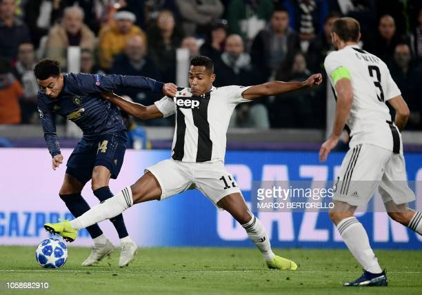 Juventus' Brazilian defender Alex Sandro tackles Manchester United's English midfielder Jesse Lingard during the UEFA Champions League group H...