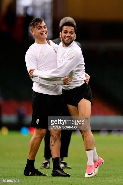 Juventus' Brazilian defender Dani Alves jokes with Juventus' Argentinian striker Paulo Dybala during a training session at The Principality Stadium...