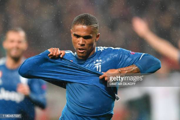 Juventus' Brazilian forward Douglas Costa celebrates after scoring a goal during the UEFA Champions League group D football match between FC...