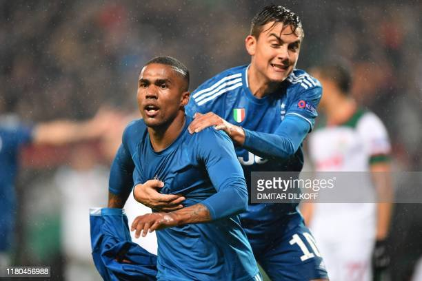 Juventus' Brazilian forward Douglas Costa celebrates with Juventus' Argentine forward Paulo Dybala after scoring a goal during the UEFA Champions...