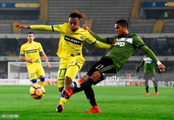 Juventus' Brazilian forward Douglas Costa centres the ball despite Chievo's Belgium midfielder Samuel Bastien during the Italian Serie A football...