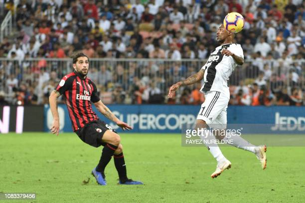 Juventus' Brazilian forward Douglas Costa controls the ball as he is marked by AC Milan's Swiss defender Ricardo Rodriguez during their Supercoppa...