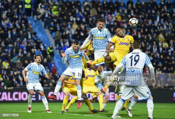 Juventu's Brazilian forward Douglas Costa fights for the ball with Spal's Italian forward Alberto Paloschi during the Italian Serie A football match...