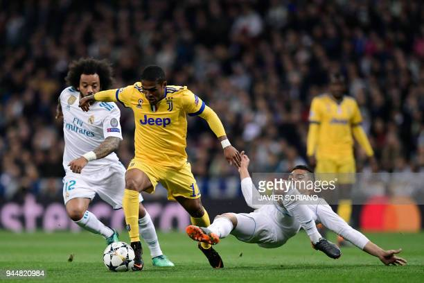 Juventus' Brazilian forward Douglas Costa vies with Real Madrid's Brazilian defender Marcelo and Real Madrid's Brazilian midfielder Casemiro during...