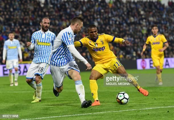 Juventu's Brazilian forward Douglas Costa vies with Spal's Slovenian midfielder Jasmin Kurtic during the Italian Serie A football match Spal vs...