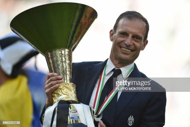 Juventus' coach from Italy Massimiliano Allegri poses with the trophy after winning the Italian Serie A football match Juventus vs Crotone and the...
