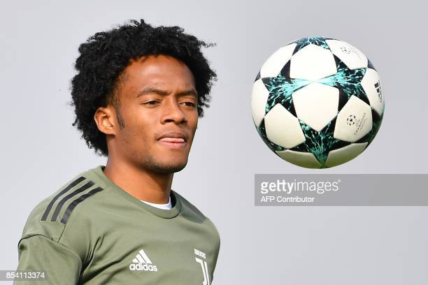 Juventus' Colombian forward Juan Cuadrado juggles with a ball during a training session on the eve of the UEFA Champions League football match...