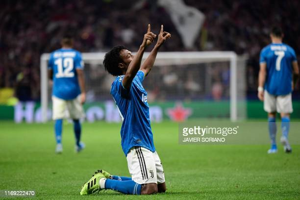 Juventus' Colombian midfielder Juan Cuadrado celebrates after scoring during the UEFA Champions League Group D football match between Atletico Madrid...