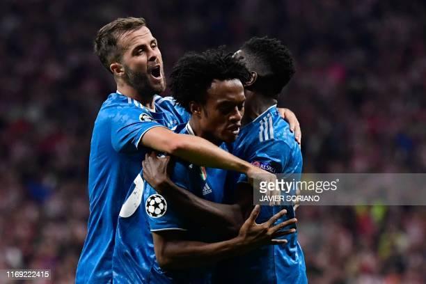 Juventus' Colombian midfielder Juan Cuadrado celebrates with Juventus' French midfielder Blaise Matuidi and Juventus' Bosnian midfielder Miralem...