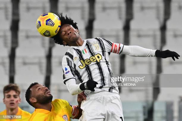 Juventus' Colombian midfielder Juan Cuadrado heads the ball during the Italian Serie A football match Juventus vs Cagliari on November 21, 2020 at...