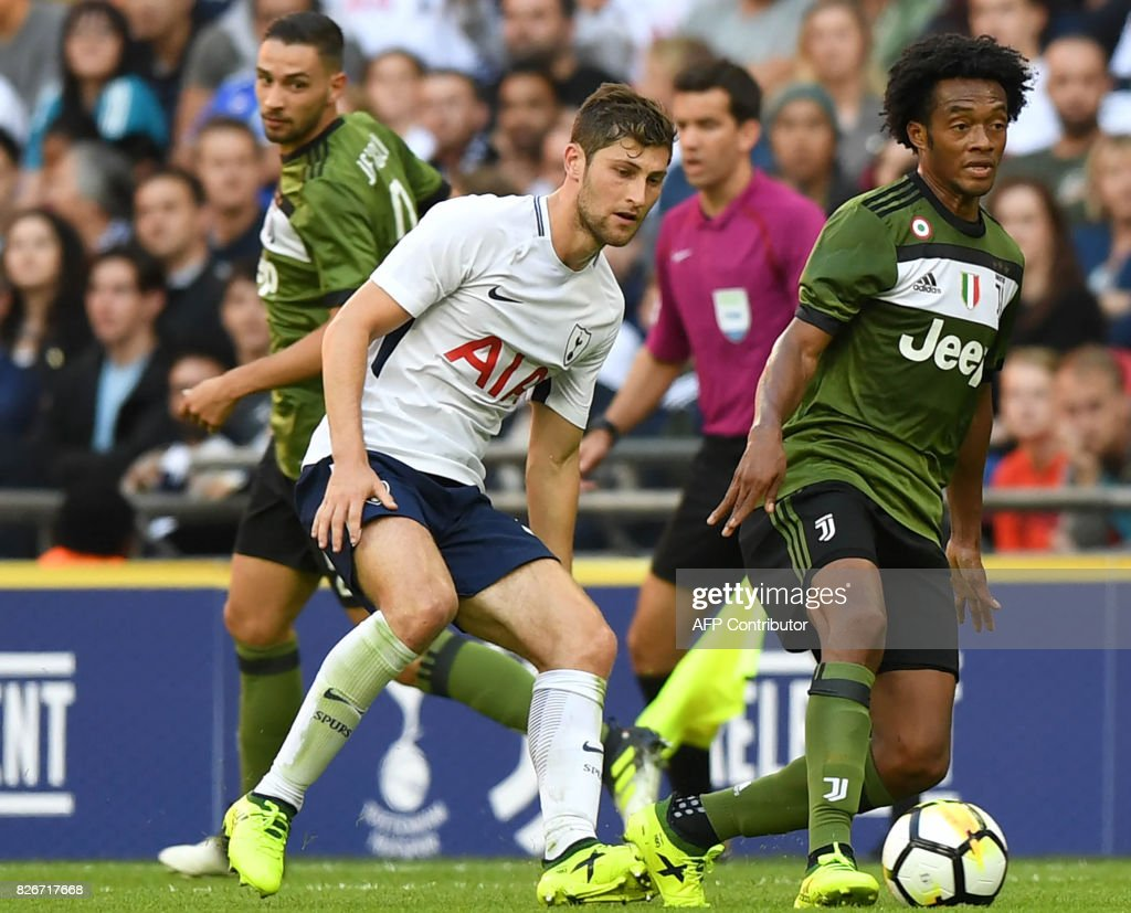 Juventus' Colombian midfielder Juan Cuadrado (R) shields the ball during the pre-season friendly football match between Tottenham Hotspur and Juventus at Wembley stadium in London on August 5, 2017. / AFP PHOTO / OLLY GREENWOOD / RESTRICTED TO EDITORIAL USE. No use with unauthorized audio, video, data, fixture lists, club/league logos or 'live' services. Online in-match use limited to 75 images, no video emulation. No use in betting, games or single club/league/player publications. /