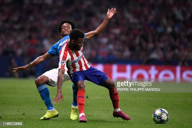 Juventus' Colombian midfielder Juan Cuadrado vies with Atletico Madrid's French midfielder Thomas Lemar during the UEFA Champions League Group D...