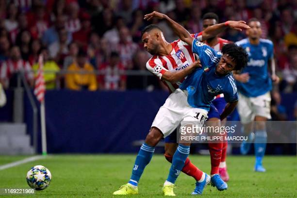 Juventus' Colombian midfielder Juan Cuadrado vies with Atletico Madrid's Brazilian defender Renan Lodi during the UEFA Champions League Group D...