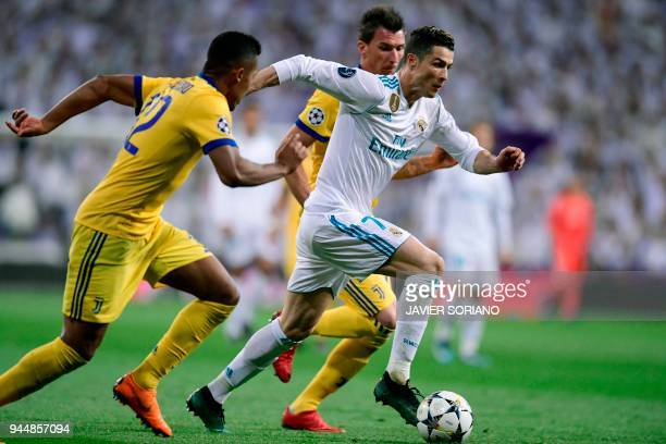 Juventus' Croatian forward Mario Mandzukic and Juventus' Brazilian defender Alex Sandro vie with Real Madrid's Portuguese forward Cristiano Ronaldo...
