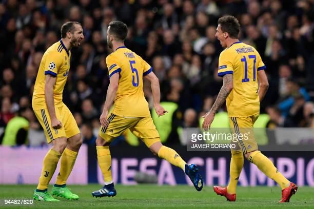 Juventus' Croatian forward Mario Mandzukic celebrates after scoring his second goal with Juventus' Italian midfielder Miralem Pjanic and Juventus'...