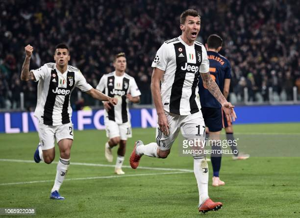 Juventus' Croatian forward Mario Mandzukic celebrates with Juventus' Portuguese defender Joao Cancelo after opening the scoring during the UEFA...