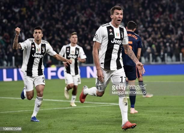 Juventus' Croatian forward Mario Mandzukic celebrates with Juventus' Portuguese defender Joao Cancelo after opening the scoring during the UEFA...