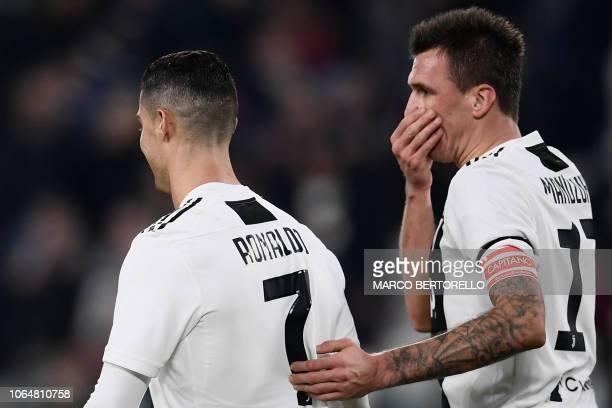 Juventus' Croatian forward Mario Mandzukic covers his mouth as he talks to Juventus' Portuguese forward Cristiano Ronaldo during the Italian Serie A...