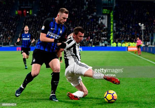 Juventus' Croatian forward Mario Mandzukic fights for the ball with Inter Milan's Slovakian defender Milan Skriniar during the Italian Serie A...
