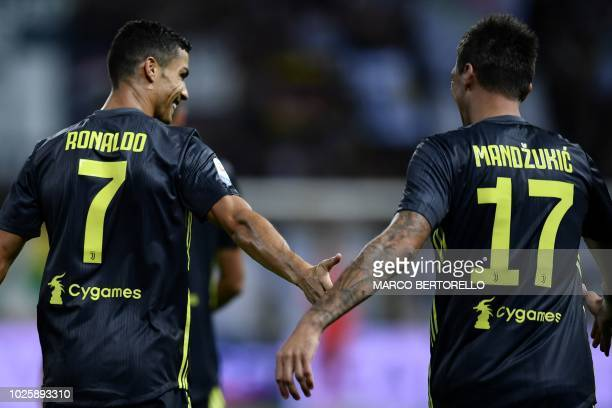 Juventus' Croatian forward Mario Mandzukic is congratulated by Juventus' Portuguese forward Cristiano Ronaldo after scoring a goal during the Italian...
