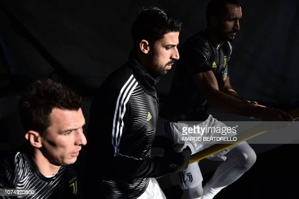 Juventus' Croatian forward Mario Mandzukic Juventus' German midfielder Sami Khedira and Juventus' Italian defender Giorgio Chiellini climb the stairs...
