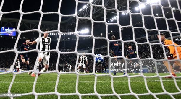 Juventus' Croatian forward Mario Mandzukic shoots to open the scoring past Valencia's Brazilian goalkeeper Neto during the UEFA Champions League...