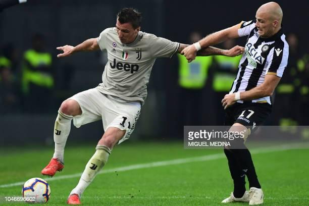 Juventus' Croatian forward Mario Mandzukic vies for the ball with Udinese's Dutch defender Bram Nuytinck during the Italian Serie A football match...