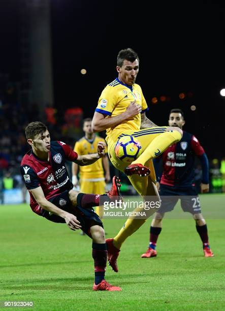 Juventus' Croatian forward Mario Mandzukic vies for the ball with Cagliari's Italian midfielder Nicolo Barella during the Italian Serie A football...