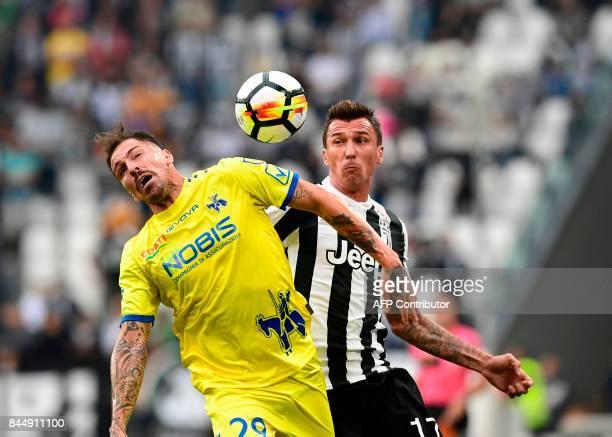Juventus' Croatian forward Mario Mandzukic vies with Chievo's Italian defender Fabrizio Cacciatore during the Italian Serie A football match Juventus...