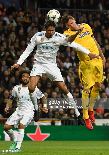 Juventus' Croatian forward Mario Mandzukic vies with Real Madrid's French defender Raphael Varane during the UEFA Champions League quarterfinal...
