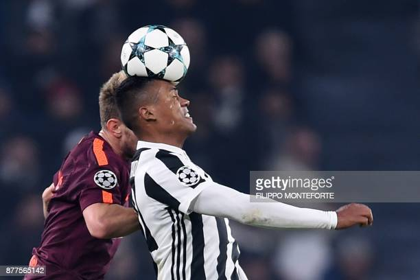 Juventus' defender from Brazil Alex Sandro and Barcelona's Croatian midfielder Ivan Rakitic jump for the ball during the UEFA Champions League Group...