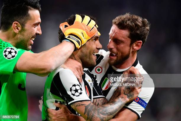 TOPSHOT Juventus Defender from Brazil Dani Alves celebrates with teammates Juventus' goalkeeper from Italy Gianluigi Buffon and Juventus' midfielder...