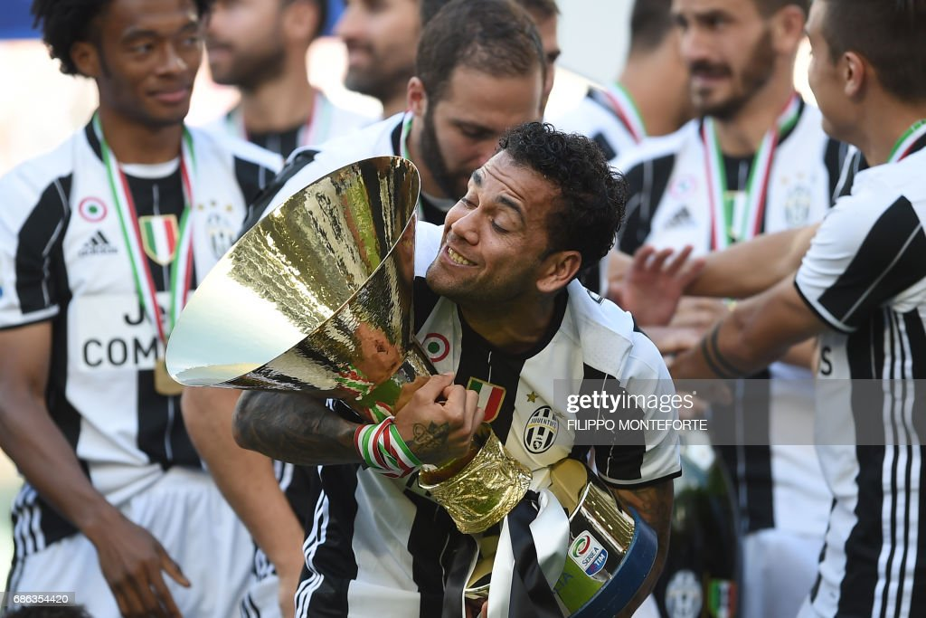 Juventus Defender from Brazil Dani Alves celebrates with the trophy after winning the Italian Serie A football match Juventus vs Crotone and the 'Scudetto' at the Juventus Stadium in Turin on May 21, 2017. First-half goals from Mario Mandzukic and Paulo Dybala, and a late header from Alex Sandro sealed a 3-0 win over Crotone to hand Juventus a record sixth consecutive Serie A title today. / AFP PHOTO / Filippo MONTEFORTE