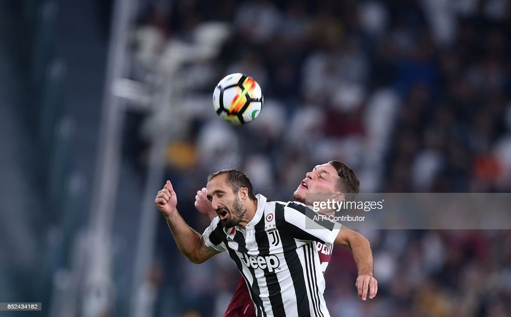 Juventus' defender Giorgio Chiellini (L) and Torino's forward Andrea Belotti go for a header during the italian Serie A football match Juventus vs Torino at the Allianz Stadium in Turin on September 23, 2017. /