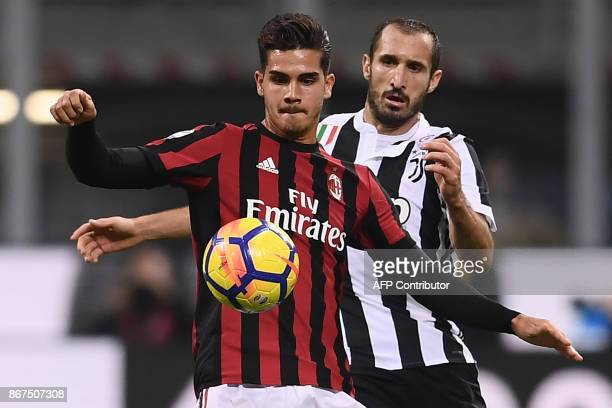 Juventus' defender Giorgio Chiellini fights for the ball with AC Milan's forward Andre Silva from Portugal during the Italian Serie A football match...