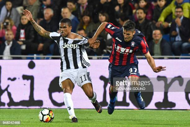 Juventus Douglas Costa vies with Crotone's Davide Faraoni during the Italian Serie A football match FC Crotone vs Juventus on April 20 2018 at the...