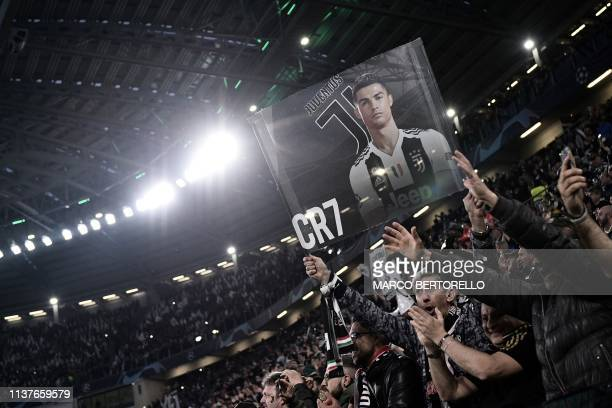 Juventus fans brandish a poster of Juventus' Portuguese forward Cristiano Ronaldo prior to the UEFA Champions League quarterfinal second leg football...