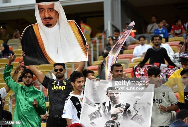Juventus fans carry a poster of Juventus' Portuguese forward Cristiano Ronaldo and a portrait of Saudi King Salman during the Supercoppa Italiana...