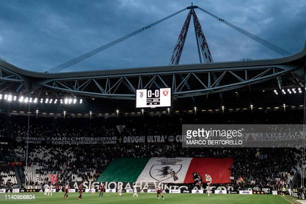 Juventus' fans hold a giant Italian flag to celebrate the Italian Scudetto during the Italian Serie A football match between Juventus and Torino on...