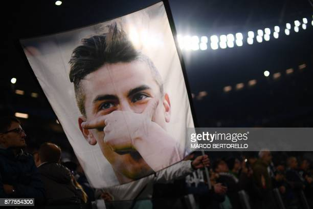 Juventus' fans wave a flag showing a portrait of Juventus' forward from Argentina Paulo Dybala before the UEFA Champions League Group D football...