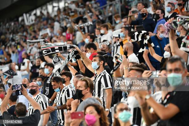 Juventus fans, wearing a face mask, cheer on their team during the Italian Serie A football match Juventus vs Empoli at Allianz Stadium in Turin, on...