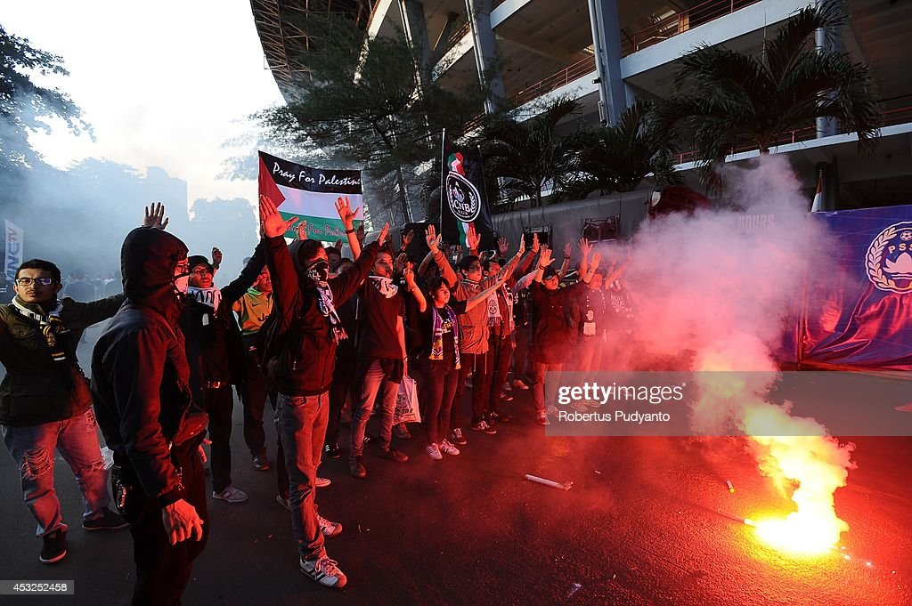 Juventus FC supporters light flares as they hold up a banner saying 'Pray for Palestine' prior to the pre season friendly match between Indonesia Selection All Star Team and Juventus FC at Gelora Bung Karno Stadium on August 6, 2014 in Jakarta, Indonesia. Juventus FC win the game 8-1.